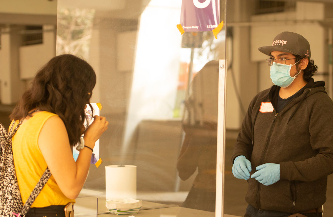 A UC Davis student provides a saliva sample to a testing kiosk worker who is wearing a face mask and gloves behind a plexiglass shield